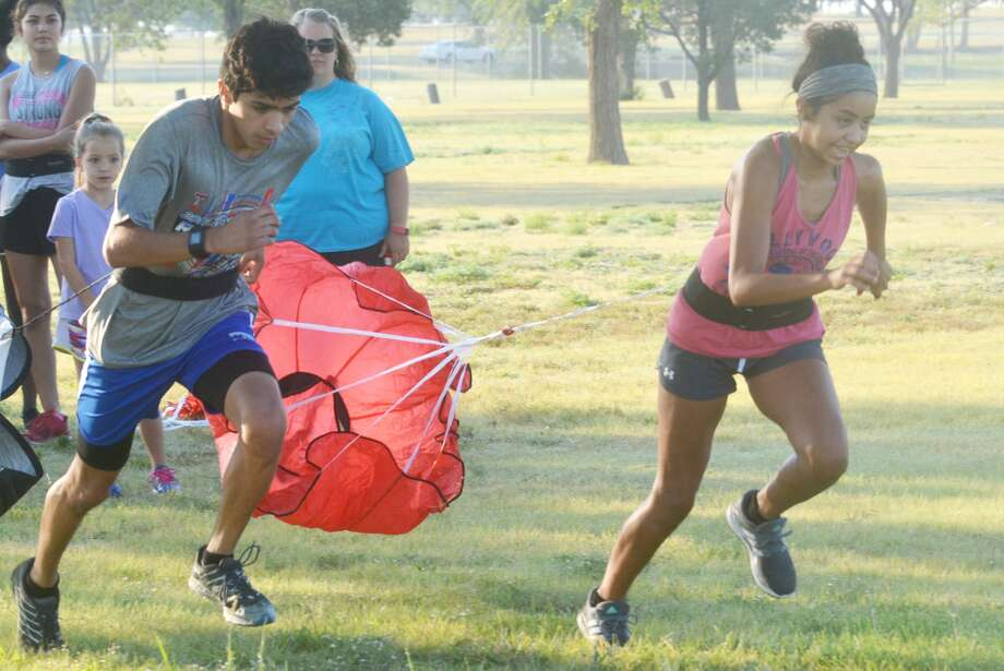"""Plainview senior cross country runners Sergio Lara, left, and Kristan Rincon start off running during a """"parachute"""" drill at practice Thursday morning. A runner must maintain enough speed to keep the attached parachute off the ground. Lara is a three-time state qualifier and Rincon has qualified once for the state meet. Photo: Skip Leon/Plainview Herald"""