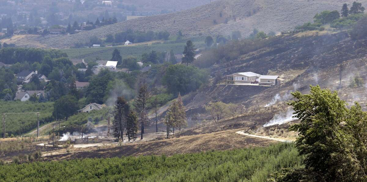 The foundation and chimneys from a destroyed home continue to smolder, lower left, in view of a home at right that survived despite the area around it being burned out from a wildfire that raced through the area the night before, Monday, June 29, 2015, in Wenatchee, Wash. The wildfires hit parts of central and eastern Washington over the weekend as the state is struggling with a severe drought, destroying dozens of structures and forcing hundreds to flee. (AP Photo/Elaine Thompson)