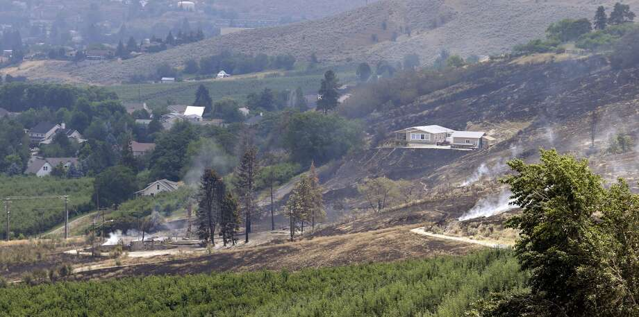 The foundation and chimneys from a destroyed home continue to smolder, lower left, in view of a home at right that survived despite the area around it being burned out from a wildfire that raced through the area the night before, Monday, June 29, 2015, in Wenatchee, Wash. The wildfires hit parts of central and eastern Washington over the weekend as the state is struggling with a severe drought, destroying dozens of structures and forcing hundreds to flee. (AP Photo/Elaine Thompson) Photo: Elaine Thompson/AP
