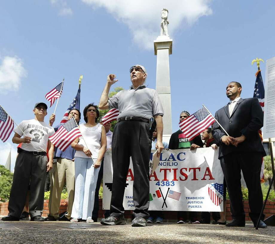 """Mario Salas of San Antonio Coalition of Human and Civil Rights (center), Bexar County 4th Precinct Commissioner Tommy Calvert (right) and others gather for a press conference to demand the Confederate monument at Travis Park be removed in light of recent efforts by Bexar County officials to take down confederate symbols on public property. Since the park is on city property, the city council would have to vote and approve such a decision. Salas and Calvert hope to persuade their city officials to take such action. The monument has been at the park since 1899 which has a statue of a confederate soldier facing South and the words, """"Our Confederate Dead"""" and """"Lest we forget"""" engraved on the monument. (Kin Man Hui/San Antonio Express-News) Photo: Kin Man Hui, Staff / San Antonio Express-News / ©2015 San Antonio Express-News"""