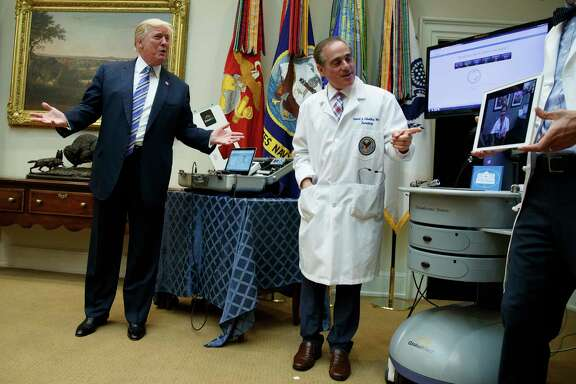 """President Donald Trump, accompanied by Veterans Affairs Secretary David Shulkin talks with a patient during a Veterans Affairs Department """"telehealth"""" event, Thursday, Aug. 3, 2017, in the Roosevelt Room of the White House in Washington. (AP Photo/Evan Vucci)"""
