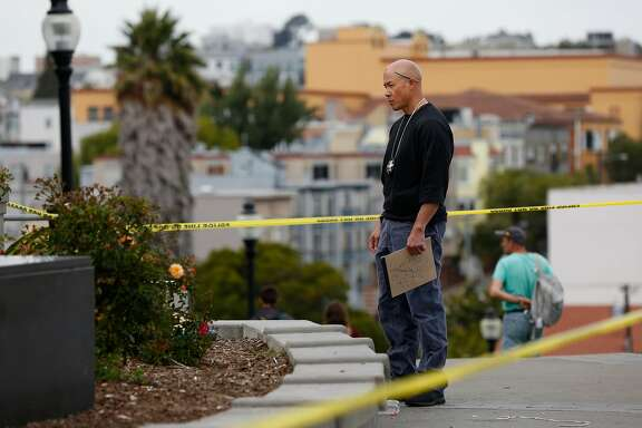 A law enforcement officer investigates an area near the scene of a shooting involving multiple people at Mission Dolores Park August 3, 2017 in San Francisco, Calif.