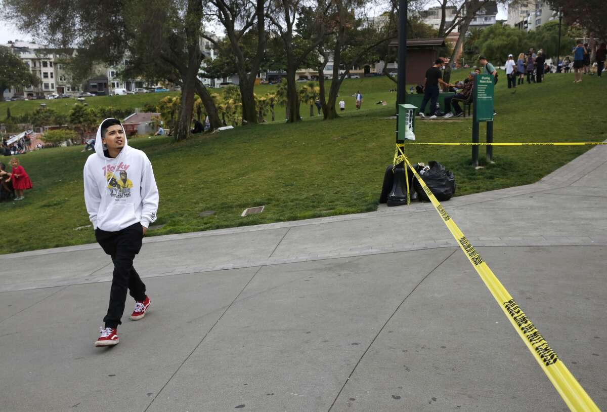 Manuel Oceguera walks past the scene of a shooting involving multiple people at Mission Dolores Park August 3, 2017 in San Francisco, Calif. Oceguera was nearby when it happened and said he heard the shots and saw people running afterward.