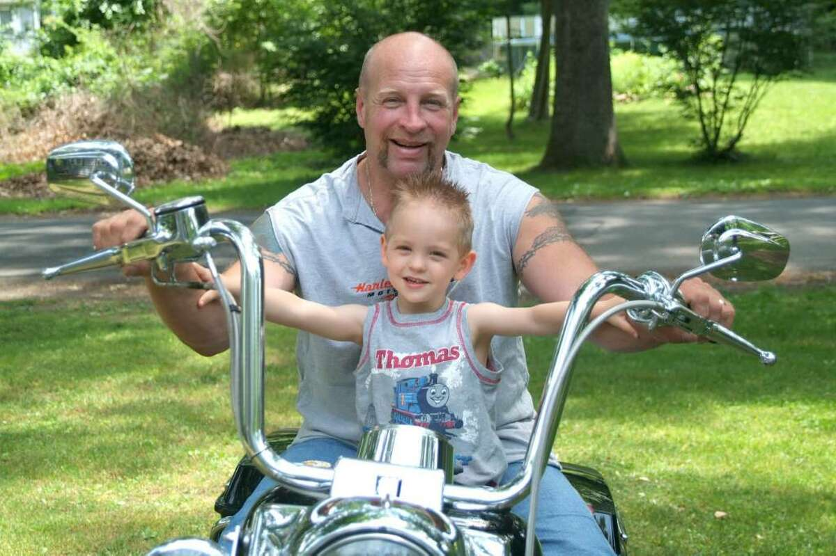 Kenny Ballard, of Sandy Hook, and his son, Kenny, 3, have some fun sitting on Dad's motorcycle. Dad is a milkman for Marcus Dairy in Danbury.