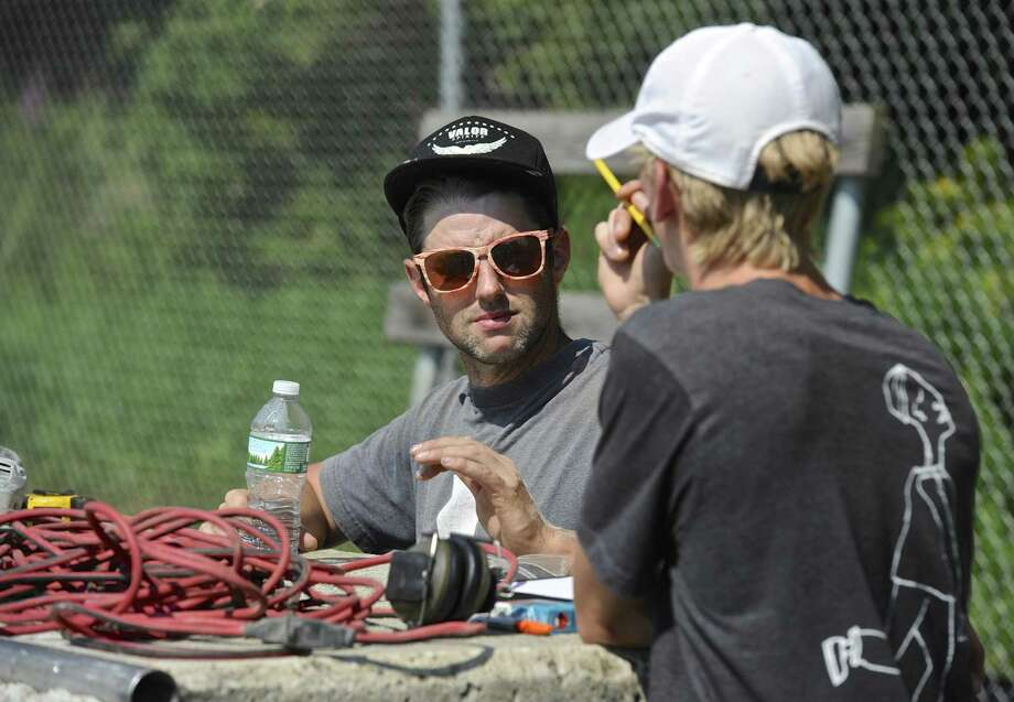 Skate park builder Dave Peterson, left, of Rampage LLC, and skateboarder Tristan Cornelis, of New Milford, go over the plans Thursday to bring the New Milford Skate Park up to code. Photo: H John Voorhees III / Hearst Connecticut Media / The News-Times