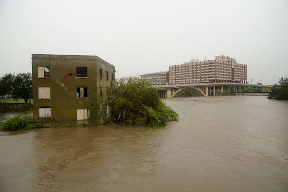The renovated building and the plaza are designed to receive water during major rain events. In this photo: The abandoned building is inundated during Hurricane Ike. Photo: Linbeck