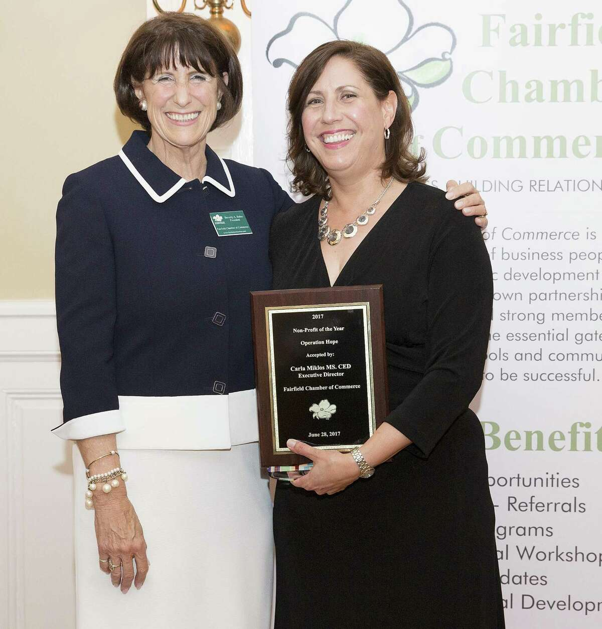 Fairfield Chamber of Commerce President Beverly Balaz, left, presents Operation Hope Executive Director Carla Miklos with the Chamber?'s Nonprofit Organization of the Year award.