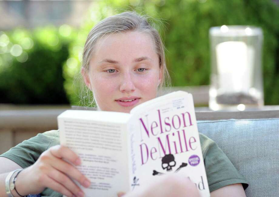 """Emma Taylor, of Fairfield, reads the book """"Plum Island"""" by author Nelson DeMille while sitting under a shade tree on Greenwich Avenue waiting for her sister to finish her dance lesson Aug. 1. Taylor said DeMille books are her favorite summer read and that she particularly likes DeMille's John Corey character, a New York City Police detective. Photo: Bob Luckey Jr. / Hearst Connecticut Media / Greenwich Time"""