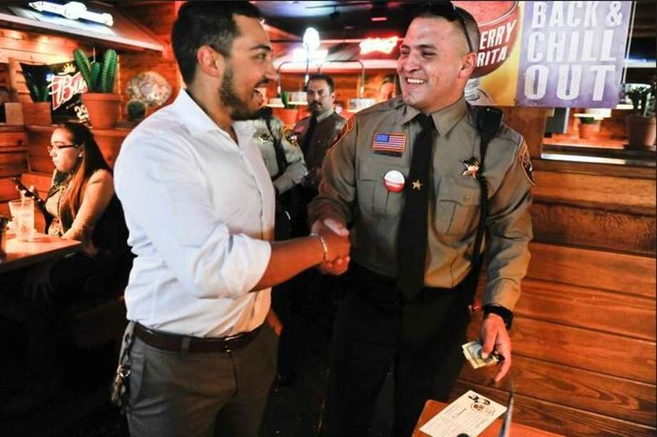 Webb County sheriff's deputy Gilbert Morales, right, collects a tip from Roy Soto on Thursday, July 20 as deputies wait tables at Texas Roadhouse during the 'Tip A Cop Night' fundraiser. The tips collected will benefit the Special Olympics. Photo: Danny Zaragoza