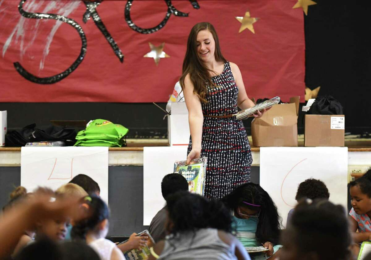 Chloe Bellcourt, a teacher in the Schenectady City School District Summer Enrichment Program at Pleasant Valley Elementary School, hands out books to her first-grade students during a book presentation at the conclusion of a four-week summer education program on Friday morning, Aug. 4, 2017, in Schenectady, N.Y. (Will Waldron/Times Union)