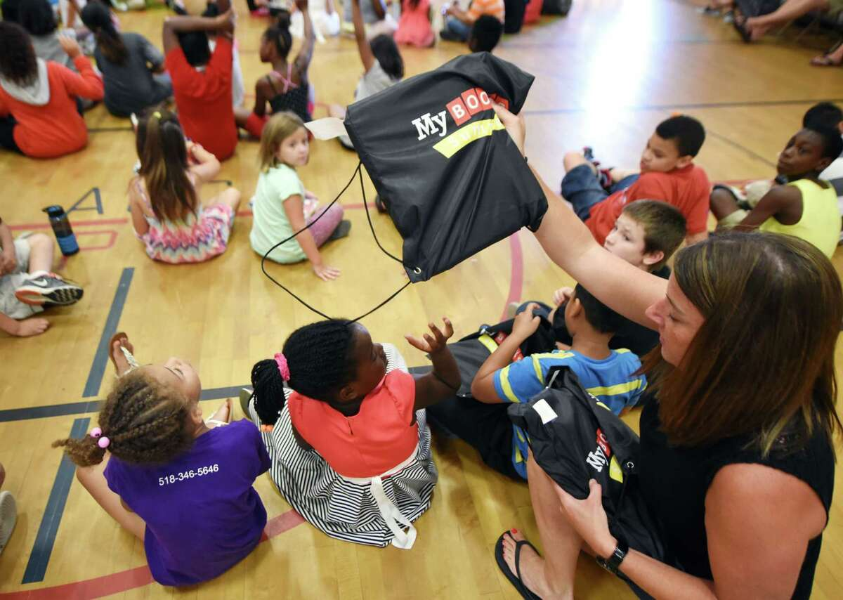 Jennifer Riley, a teacher in the Schenectady City School District Summer Enrichment Program at Pleasant Valley Elementary School, hands out books to her second-grade students during a book presentation at the conclusion of a four-week summer education program on Friday morning, Aug. 4, 2017, in Schenectady, N.Y. (Will Waldron/Times Union)