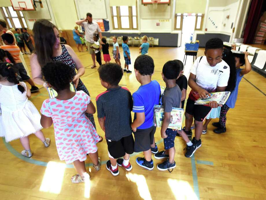 Chloe Bellcourt, a teacher in the Schenectady City School District Summer Enrichment Program at Pleasant Valley Elementary School, leads her first-grade students back to class with books they received following a presentation at the conclusion of a four-week summer education program on Friday morning, Aug. 4, 2017, at Pleasant Valley Elementary School, in Schenectady, N.Y. (Will Waldron/Times Union) Photo: Will Waldron, Albany Times Union / 20041212A