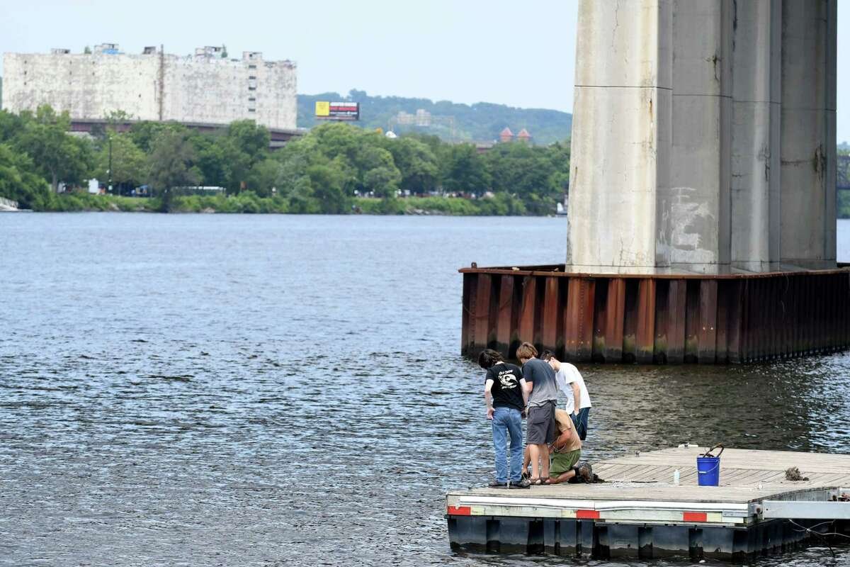 Dave Stacey of Coeymans, kneeling, goes magnet fishing with family and friends at Riverfront Park on Thursday, Aug. 3, 2017, in Rensselaer, N.Y. Powerful magnets attached to cables are dropped into the river to see what they can haul out. (Will Waldron/Times Union)