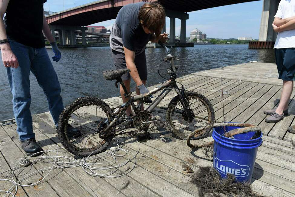Druhan Stacey of Coeymans examines a bicycle that he fished from the Hudson River at Riverfront Park on Thursday, Aug. 3, 2017, in Rensselaer, N.Y. Powerful magnets attached to cables are dropped into the river to see what they can haul out. (Will Waldron/Times Union)