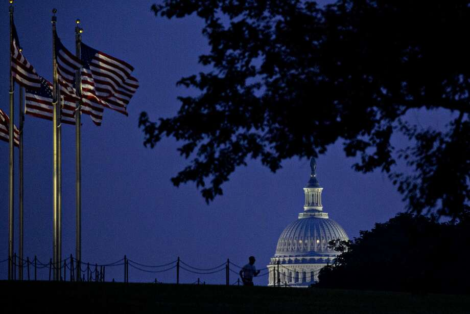 The U.S. Capitol stands past American flags flying at the Washington Monument on July 28. Photo: Andrew Harrer, Bloomberg