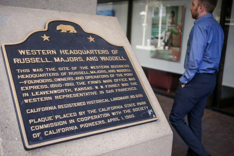 A man walks past a plaque on 601 Montgomery noting the terminus of the Pony Express in San Francisco. Photo: Nicole Boliaux, The Chronicle