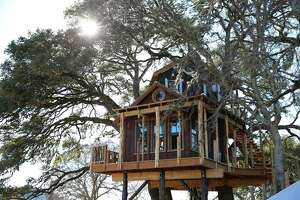"""""""Treehouse Masters"""" created this Western-themed rustic beauty amid towering oaks in the Hill Country."""