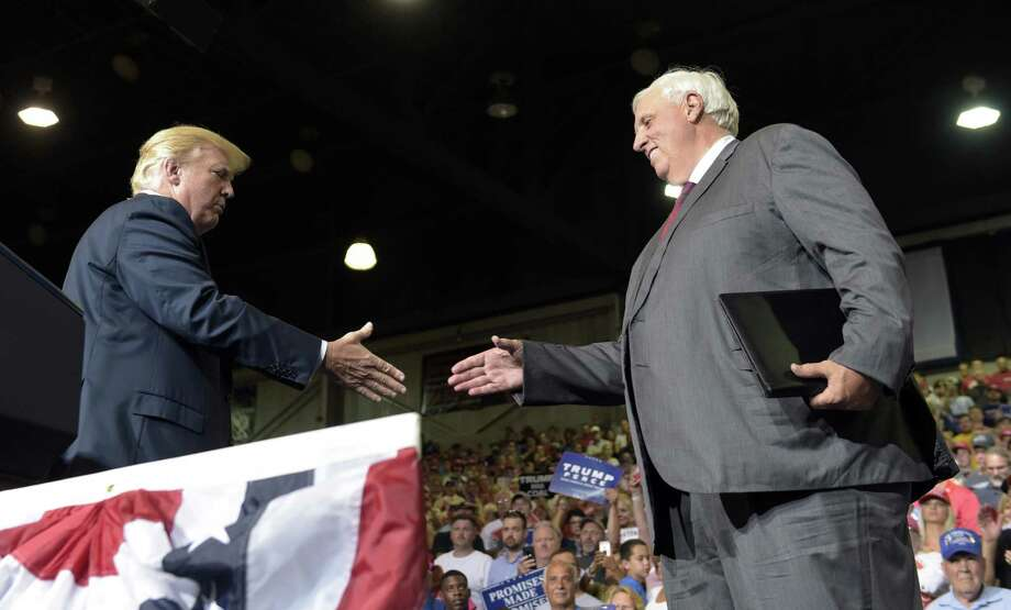 President Donald Trump, left, reaches out to shake hands with West Virginia Gov. Jim Justice, right, at a campaign-style rally at Big Sandy Superstore Arena in Huntington, W.Va., Thursday, Aug. 3, 2017, where Justice announced that he is changing parties to be a Republican . (AP Photo/Susan Walsh) Photo: Susan Walsh / Associated Press / Copyright 2017 The Associated Press. All rights reserved.