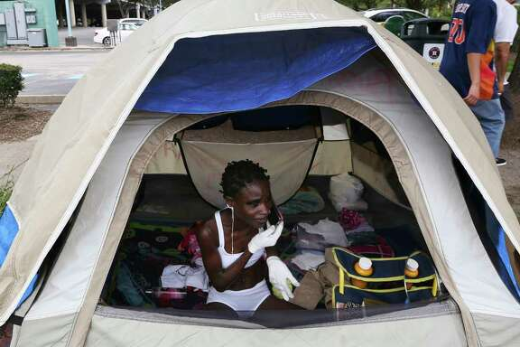 Houston Astros fans walk pass by Oluwabusayo Franccessca Osho, claims to be from Nigeria, who lives in a tent just outside of Minute Maid Park Saturday, June 10, 2017, in Houston. ( Yi-Chin Lee / Houston Chronicle )