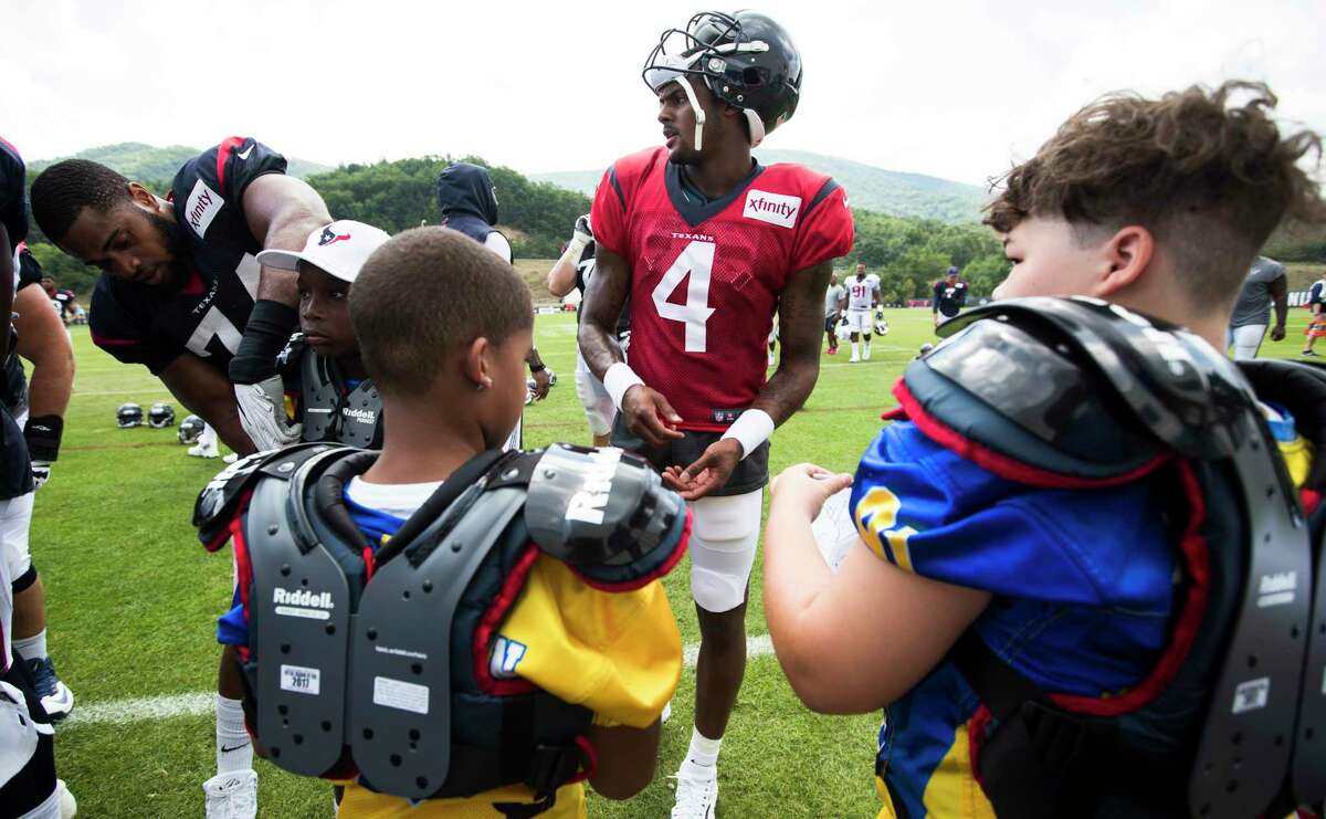 Houston Texans offensive tackle Chris Clark (74) and quarterback Deshaun Watson (4) sign autographs as they help hand out shoulder pads to kids from West Virginia Youth Football League following training camp practice at the Greenbrier on Friday, Aug. 4, 2017, in White Sulphur Springs, W.Va.