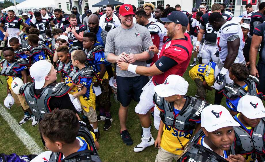 Houston Texans defensive end J.J. Watt, center, and quarterback Tom Savage, right, talk as they help hand out shoulder pads to kids from West Virginia Youth Football League following training camp practice at the Greenbrier on Friday, Aug. 4, 2017, in White Sulphur Springs, W.Va. Photo: Brett Coomer, Houston Chronicle / © 2017 Houston Chronicle}