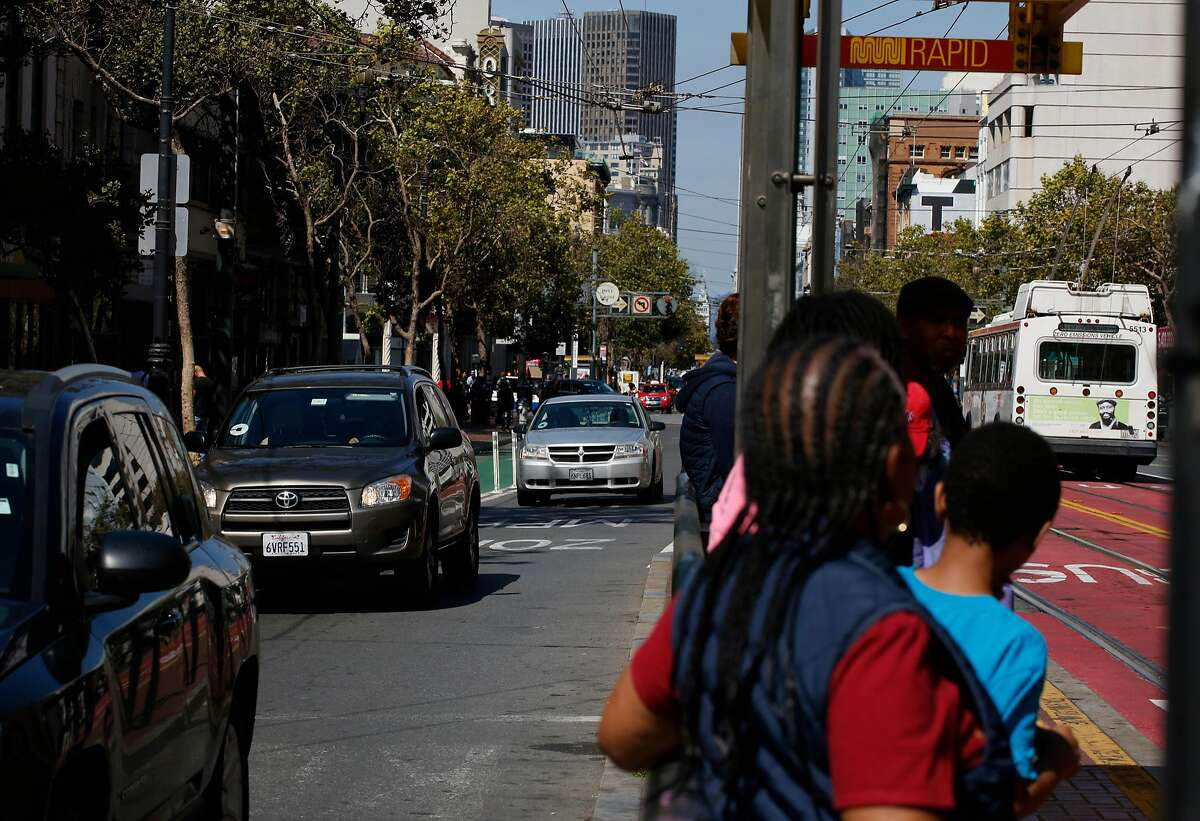 Cars and cyclists pass pedestrians on 9th and Market Street. San Francisco is planning a new design for Market that would ban private cars and add bike lanes.