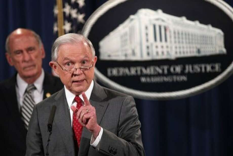 "U.S. Attorney General Jeff Sessions speaks as Director of National Intelligence Dan Coats listens during an event at the Justice Department on Friday. Sessions held the event to discuss ""leaks of classified material threatening national security."" Photo: Alex Wong, Getty Images"