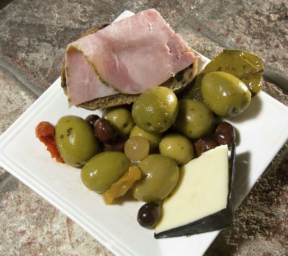 Spanish olives are plated with manchego and jambon on olive bread. The Commerce Department is investigating whether Spain is dumping its olives — specifically the mild, slightly drier black types used in sandwiches, salads and pizzas — on the U.S. market. Photo: Contra Costa Times File Photo / Contra Costa Times