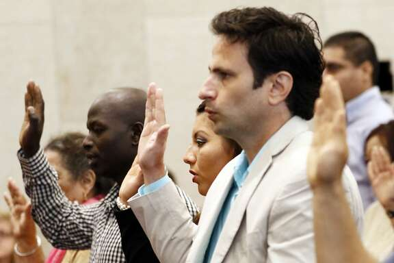 Dasiel Rodriquez, of Cuba, right, Ingrid Sharpe of Mexico, and Robert Kipkorir Rono of Kenya, were among 33 immigrants who recited the Oath of Allegiance to the United States of America during a naturalization ceremony at the federal courthouse in Jackson, Miss., Thursday July 6, 2017. The ceremony was the culmination of a period of application, civics and English testing, an interview and a background check, among the steps leading to the recitation of the oath and their presentation of citizen certificates. (AP Photo/Rogelio V. Solis)