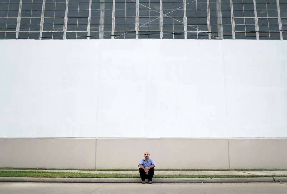 "Houston artist Mario Figueroa, Jr., also known as ""Gonzo247,"" poses for a portrait at the Harris County Records Building, at 5900 Canal St., Thursday, Aug. 3, 2017, in Houston. In 1973, artist Leo Tanguma painted a large mural titled, ""The Rebirth of Our Nationality,"" on the exterior wall of the building. After years of deterioration, the original mural was whitewashed, and Figueroa was chosen to repaint the it.  ( Jon Shapley  / Houston Chronicle ) Photo: Jon Shapley, Staff / © 2017 Houston Chronicle"