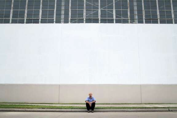 "Houston artist Mario Figueroa, Jr., also known as ""Gonzo247,"" poses for a portrait at the Harris County Records Building, at 5900 Canal St., Thursday, Aug. 3, 2017, in Houston. In 1973, artist Leo Tanguma painted a large mural titled, ""The Rebirth of Our Nationality,"" on the exterior wall of the building. After years of deterioration, the original mural was whitewashed, and Figueroa was chosen to repaint the it.  ( Jon Shapley  / Houston Chronicle )"