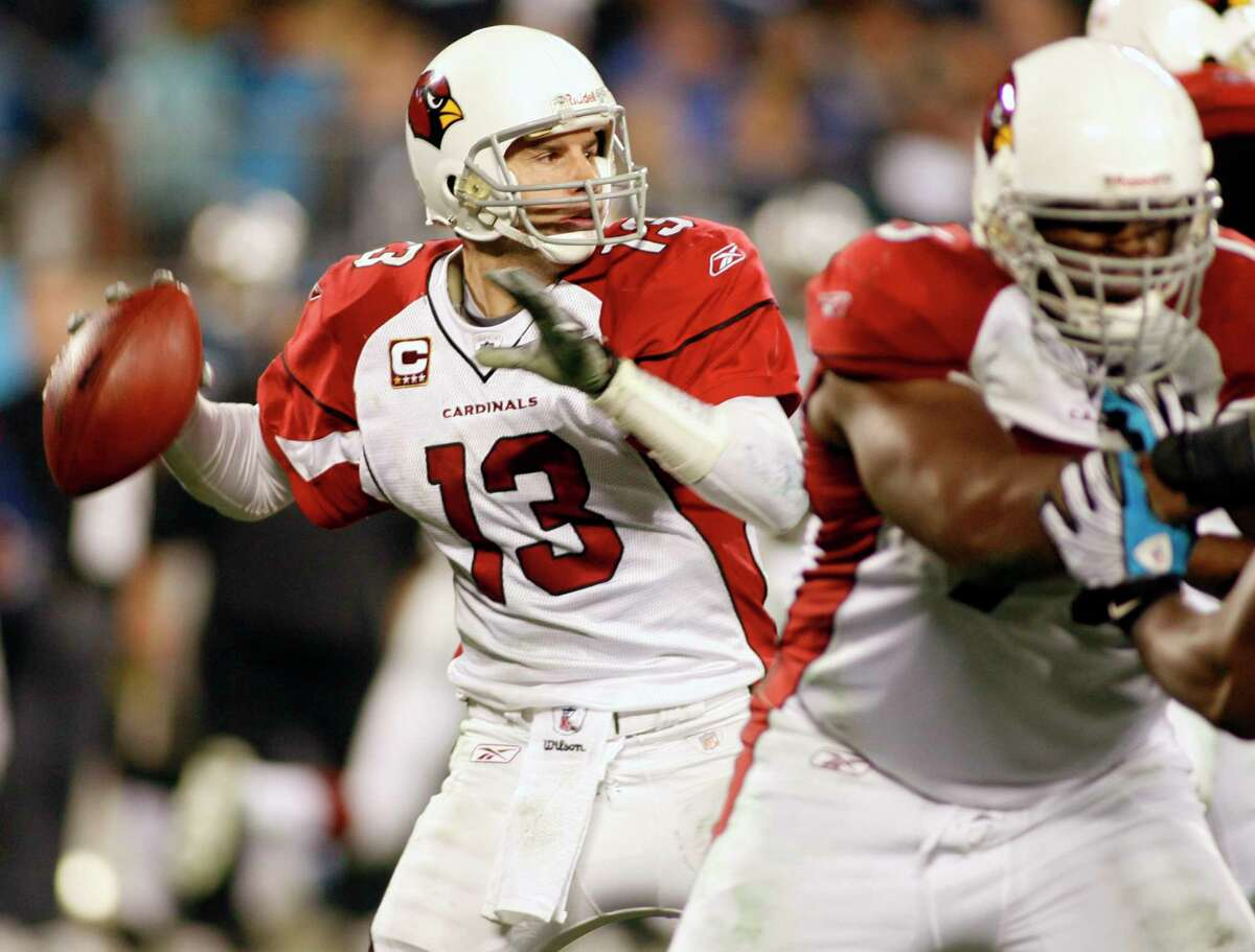 In this Jan. 10, 2009 file photo, Arizona Cardinals quarterback Kurt Warner (13) prepares to throw a pass during an NFL divisional playoff football game in Charlotte, N.C.