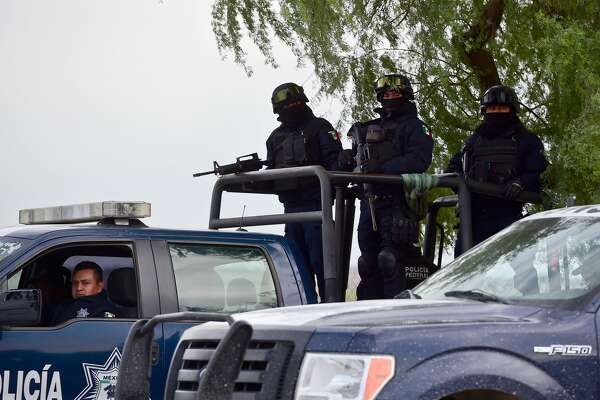 Federal Police vehicles stand by at the gang-infested Matamoros-Ciudad Victoria highway, Tamaulipas State, Mexico, in the border with the United States, on December 17, 2015.
