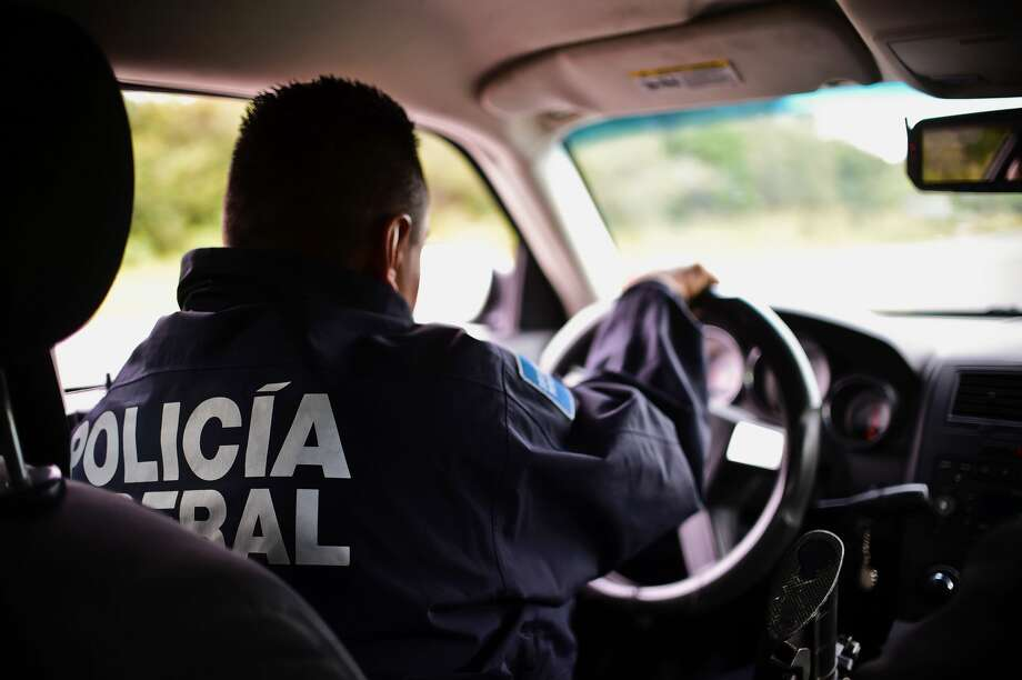 Federal Police patrol car escorting vehicles with civilians along the gang-infested Matamoros-Ciudad Victoria highway, Tamaulipas State, Mexico, in the border with the United States, on December 17, 2015. Photo: RONALDO SCHEMIDT/AFP/Getty Images
