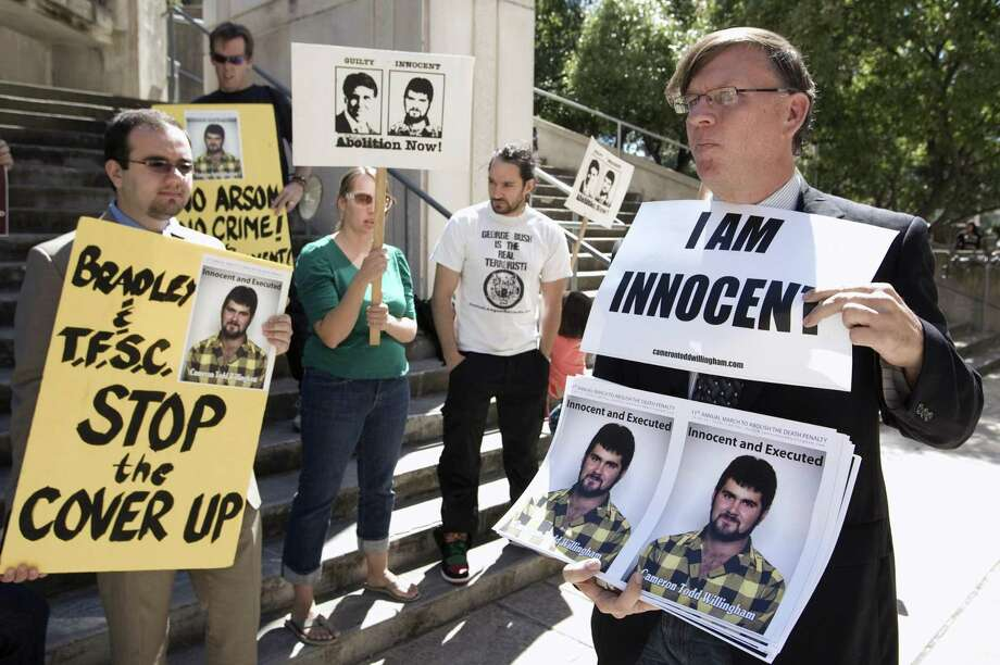 People protest before a hearing about the Cameron Todd Willingham case in Austin in 2010. It is likely that Willingham was wrongly convicted — and executed — because of junk science and  a jailhouse informant who has since recanted. Photo: Associated Press File Photo / Austin American-Statesman