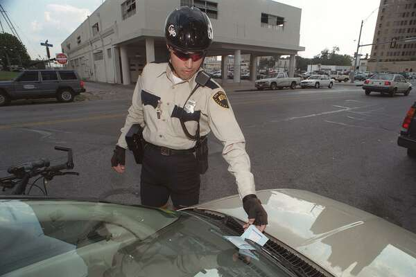 A parking enforcement officer writes a ticket downtown in 1995. Tickets have surged in the past few months, but signage warning drivers has not.