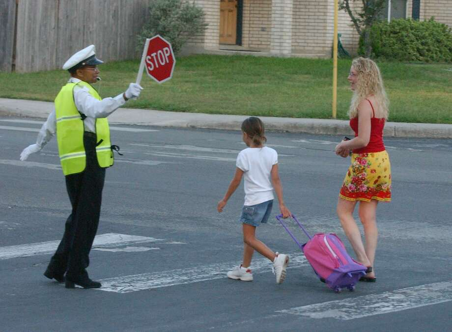 Crossing guard, Dolores Herron stops traffic as Charli Valadez walks her daughter, Leslie, 9, to Scobee Elementary School Wednesday morning in 2003. With start dates varying across the county, motorists should just figure on slowing down in every school zone. Photo: ROBERT MCLEROY /EXPRESS-NEWS FILE PHOTO / SAN ANTONIO EXPRESS-NEWS