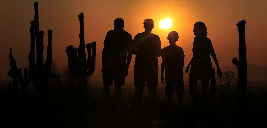 Spectators look toward the setting sun to view the 2012 solar eclipse. Photo: Ross D. Franklin, Associated Press