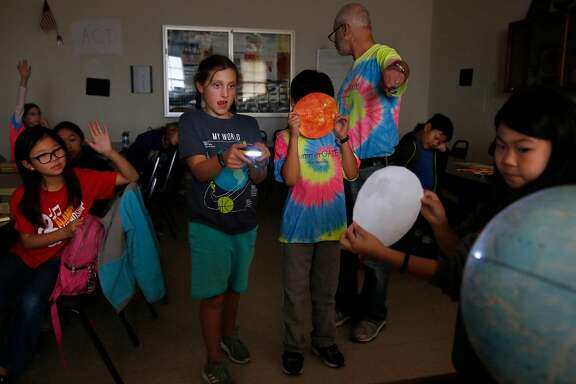 From left, Stephanie Li, 10, watches with other students as Raya Gottsfeld, 10, holds a flashlight simulating the sun's rays for Christopher Gee, 11, as he holds a picture of the sun while Saya Tarm, 9, holds a picture of the moon and moves it across the globe representing the earth, thereby simulating what happens to cause a solar eclipse as their teacher Alex Hertz explains it during a SummerGATE class at St. Anne's campus August 3, 2017 in San Francisco, Calif.