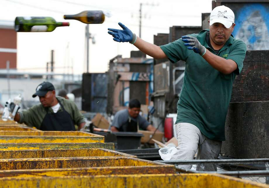 A man tosses wine bottles into large bins at the Our Planet Recycling collection center on Bayshore Boulevard in San Francisco, Calif. on Thursday, Aug. 3, 2017. Independent recycling centers are struggling to stay open saying the state subsidies aren't enough to keep them in business. Photo: Paul Chinn, The Chronicle