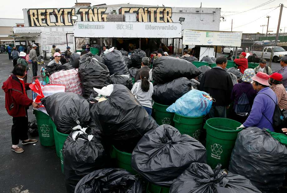 Top: Customers line up to have goods weighed before they receive a cash payment at a collection center on Bayshore Boulevard. Above: A customer tosses wine bottles into a bin at the center. Photo: Paul Chinn, The Chronicle
