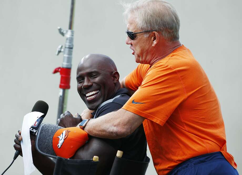Denver Broncos general manager John Elway, right, hugs former teammate and NFL Hall of Fame inductee for 2017, Terrell Davis, as he waits to interview Elway for a television spot during drills at an NFL football training camp Sunday, July 30, 2017, in Englewood, Colo. (AP Photo/David Zalubowski) Photo: David Zalubowski, Associated Press