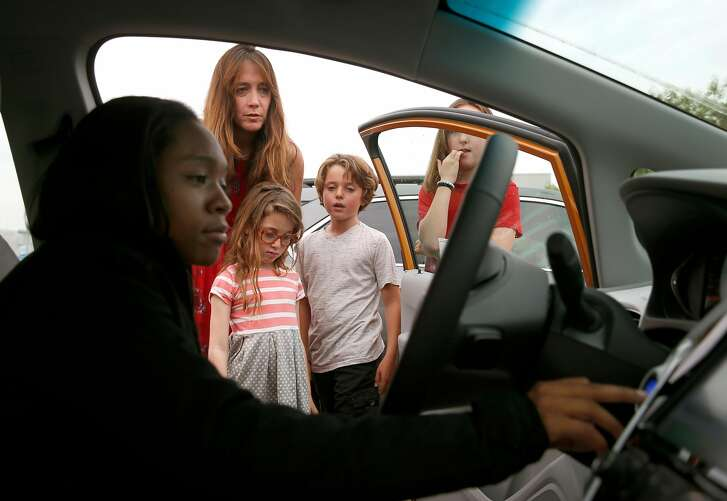 Sales associate Devani Knox (left) explains functions of the Bolt EV all-electric car to Dana Nachman and her children Sidney, 7, Charlie, 10, and Annie, 11, after a test drive at a Chevrolet dealership in Fremont, Calif. on Friday, Aug. 4, 2017. Proposed state legislation may provide instant rebates to boost sales of plug-in vehicles.