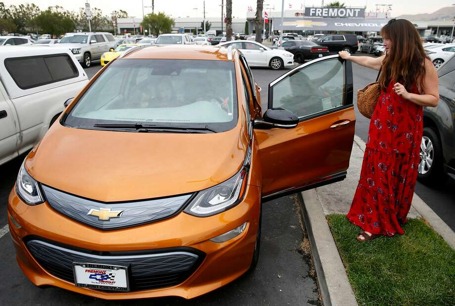 Dana Nachman gets a second look at the all-electric Bolt after taking a test drive with her three children at a Chevrolet dealership in Fremont. Proposed state legislation would revamp and expand California's existing rebate program for buyers of electric or plug-in hybrid cars. Photo: Paul Chinn, The Chronicle