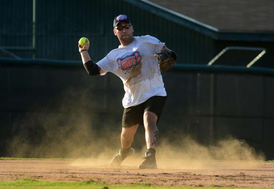 """Montgomery County Sheriff's Office shortstop Daniel Pena makes a play against a Woodlands Fire Department hitter during the """"Boots and Badges"""" event which pitted the two teams in a friendly game of softball at Scotland Yard on the campus of McCullough Junior High School on Aug. 8,2015. Photo: Jerry Baker, Freelance"""
