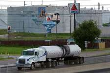An oil tanker passes storage tanks at the Citgo Refinery in Corpus Christi, Texas, on Thursday, August 10, 2006. Citgo Petroleum Corp., the U.S. refining arm of Venezuela's state oil company, was indicted for benzene emissions at a refinery and for failing to protect migratory birds that became coated in oil at a storage facility. A federal grand jury in Corpus Christi, Texas, issued a 10-count indictment, charging Citgo, its Citgo Refining subsidiary and Philip Vrazel, environmental manager of the company's Corpus Christi East refinery, with criminal violations of the Clean Air Act and the Migratory Bird Treaty Act. Photographer: Eddie Seal/Bloomberg News.