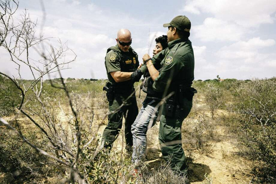 Border Patrol agents Michael Johnson, left, and Christian Salmon apprehend a Honduran national who crossed the Rio Grande in an inflatable raft near Roma, Texas, May 15, 2017. Surveillance towers, drones, helicopters and unmanned blimps are all being used here to build a virtual wall, one which some experts say can be as effective as a physical one, at far lower cost. (William Widmer/The New York Times) Photo: WILLIAM WIDMER, STR / NYT / NYTNS
