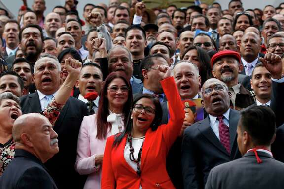 The president of Venezuela's Constituent Assembly Delcy Rodriguez, front and center, leads the newly sworn-in members as they pose for a photo Friday.