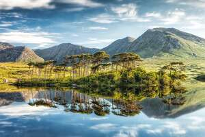 The still waters of Derryclare Lough in Connemara with the mountains in the background in Ireland.