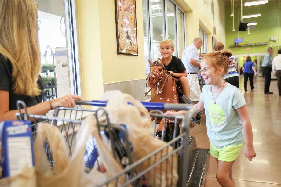 Montgomery resident Jael Karl, left, looks on as her children Will, 5, center, and Carlee, 7, right, play on a coin-operated riding horse at the end of their grocery shopping trip on Friday at the Kroger Marketplace in Montgomery. Karl said that she was excited for the opening of the new Kroger, citing reasons like low prices, variety of options and bonuses like fuel points. Photo: Michael Minasi, Staff Photographer / © 2017 Houston Chronicle